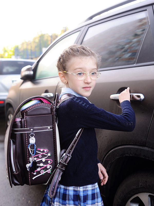 Girl with backpack getting into a car